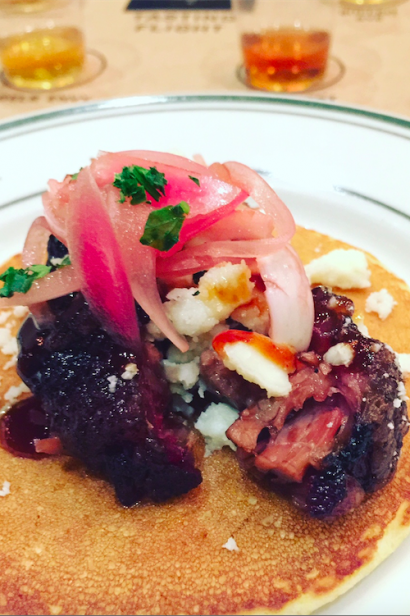 BBQ brisket and pickled red onion on a corn cake