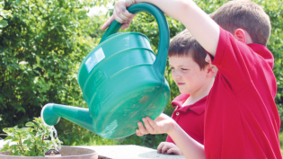Two Young Boys Watering School Plants